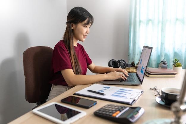 Une jeune fille asiatique belle entreprise de détente utilise un ordinateur portable travaillant à distance de la maison