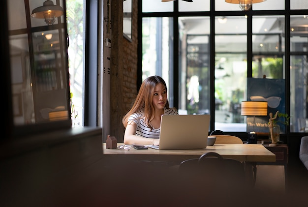 Jeune fille asiatique commence à travailler avec un ordinateur portable au café