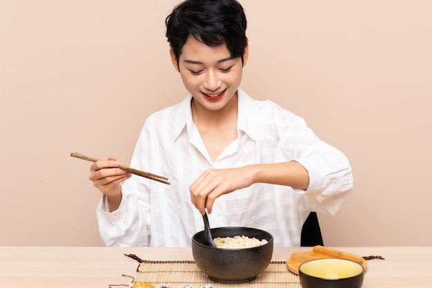 Jeune fille asiatique dans une table avec bol de nouilles et sushi