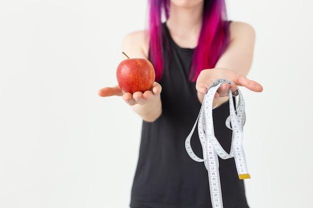 Jeune fille asiatique floue hipster cheveux colorés tenant en mains un ruban à mesurer et apple posant sur un fond blanc. concept de saine alimentation. espace publicitaire.