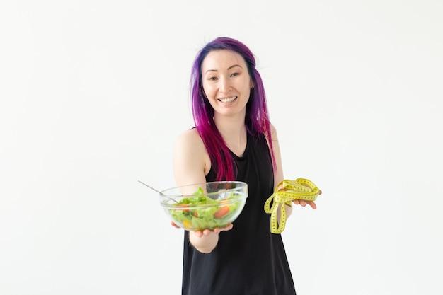 Jeune fille asiatique hipster cheveux colorés tenant en mains un ruban à mesurer et salade de légumes posant sur un fond blanc. concept de saine alimentation. espace publicitaire