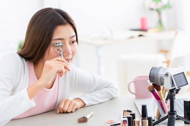 Jeune fille asiatique influenceuse de beauté enregistre une vidéo tout en utilisant un recourbe-cils à la maison