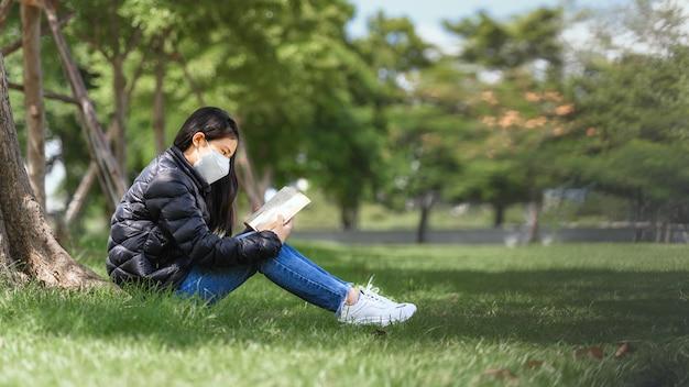Une jeune fille asiatique a l'intention de lire un livre pour préparer l'examen de test final assis sous les arbres du parc en plein air pendant l'heure d'apprentissage en été. éducation apprentissage étudier le concept.