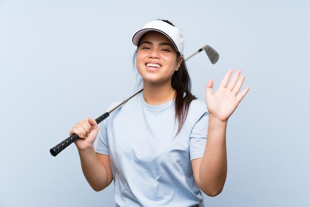 Jeune fille asiatique jeune golfeur sur mur bleu isolé, saluant avec main avec expression heureuse