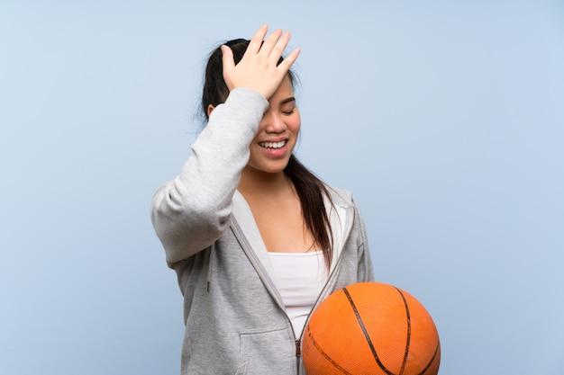 Jeune fille asiatique jouant au basketball sur un mur isolé a réalisé quelque chose et avait l'intention de la solution