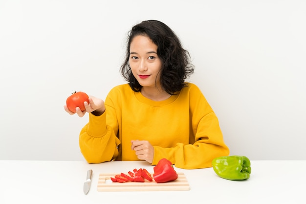Jeune fille asiatique avec des légumes dans une table