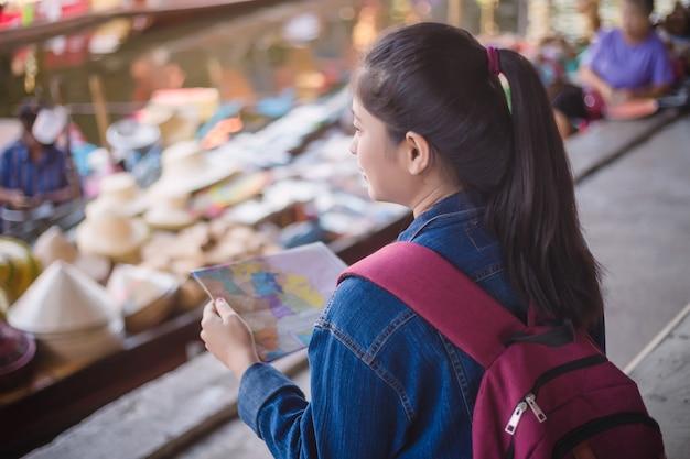 Jeune fille asiatique marchant au marché flottant de dumonoe saduak, thaïlande