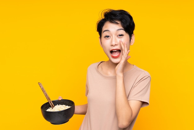 Jeune fille asiatique sur mur jaune isolé criant avec la bouche grande ouverte tout en tenant un bol de nouilles avec des baguettes