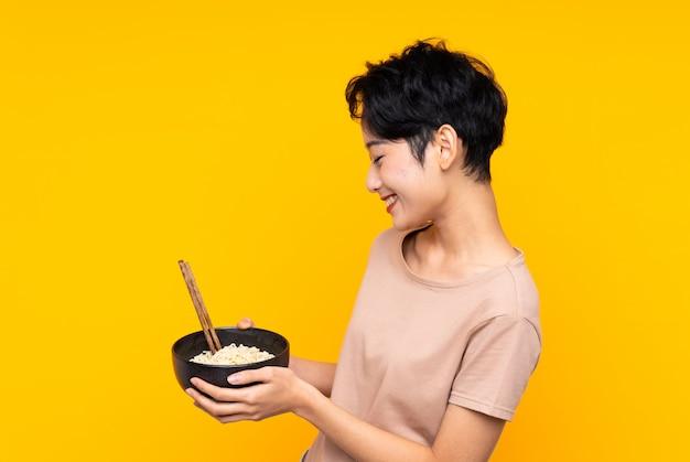 Jeune fille asiatique sur mur jaune isolé avec une expression heureuse tout en tenant un bol de nouilles avec des baguettes
