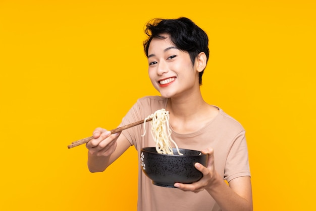 Jeune fille asiatique sur un mur jaune isolé tenant un bol de nouilles avec des baguettes et l'offrant