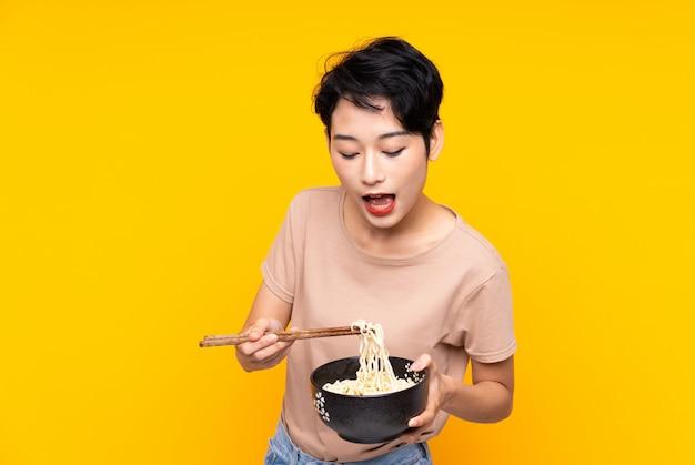 Jeune fille asiatique sur mur jaune isolé tenant un bol de nouilles avec des baguettes