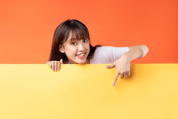 Jeune fille asiatique pointant son doigt vers le bas sur jaune et orange