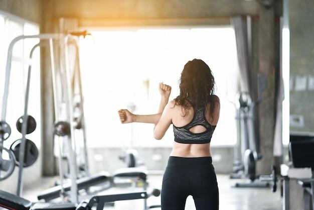 Jeune fille asiatique qui s'étend dans la salle de gym