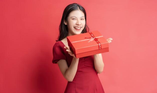 Jeune fille asiatique en robe tenant une boîte cadeau rouge avec une expression joyeuse sur fond