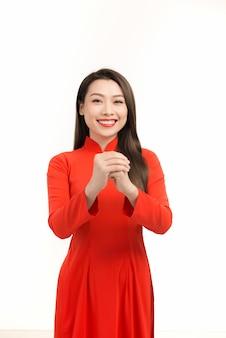 Jeune fille asiatique en robe traditionnelle ao dai souriante et saluant, célébrant le nouvel an lunaire ou la fête du printemps