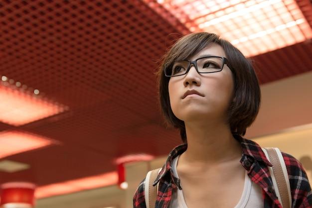 Jeune fille asiatique à la rue dans la ville moderne.