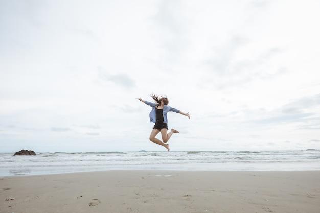 Jeune fille asiatique sautant sur le san par la plage