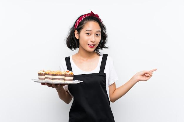 Jeune fille asiatique tenant beaucoup de gâteau à muffins sur mur blanc isolé surpris et pointant le doigt sur le côté