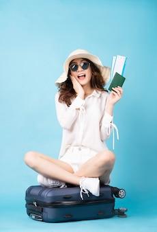 Jeune fille asiatique tenant un billet d'avion et un téléphone assis sur une valise