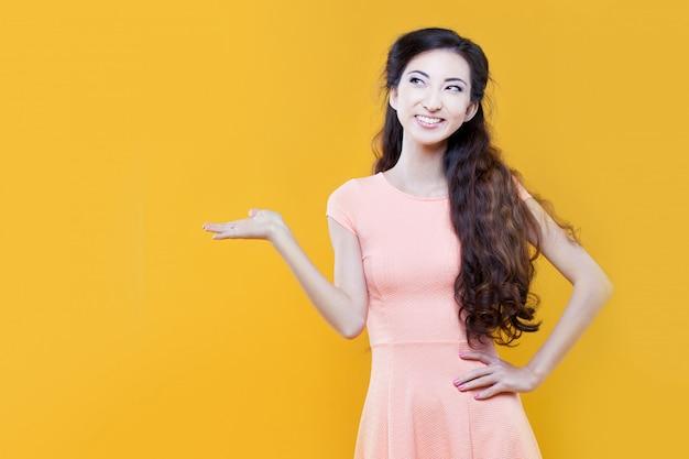 Jeune fille asiatique tenant quelque chose dans la main, placez votre texte. portrait sur jaune.