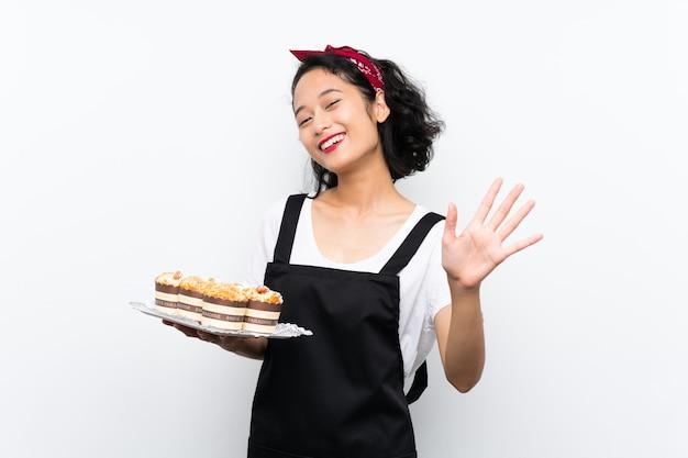 Jeune, fille asiatique, tenue, beaucoup, gâteau muffin, sur, blanc, mur, saluer, à, main, à, expression heureuse