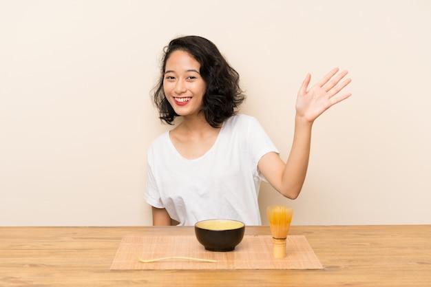 Jeune fille asiatique avec thé matcha, saluant avec la main avec une expression heureuse