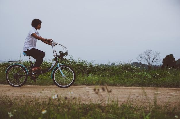 Jeune fille asiatique avec vélo vintage dans le paysage de campagne nature.