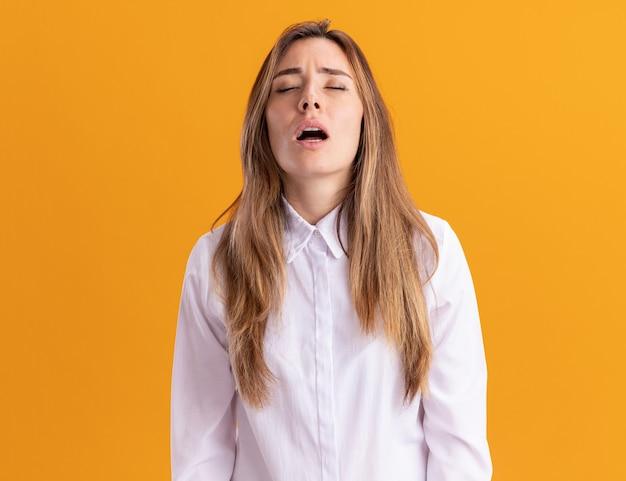 Une jeune fille assez caucasienne fatiguée se tient les yeux fermés