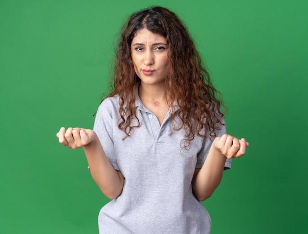 Jeune fille assez caucasienne mécontente, pinçant les lèvres faisant un geste d'argent