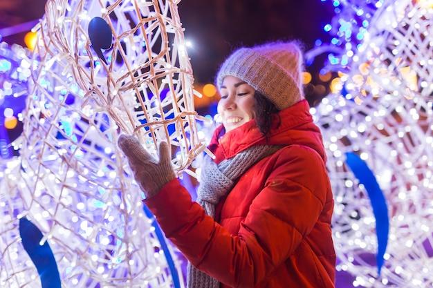 Jeune fille assez drôle s'amusant en plein air en hiver. concept de vacances de noël, de ville et d'hiver.