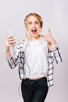 Jeune fille assez gaie avec smartphone à la main. joyeuse blonde magnifique de bonne humeur en écoutant de la musique, en montrant un bon signe et en riant. émotions passionnantes. la satisfaction.
