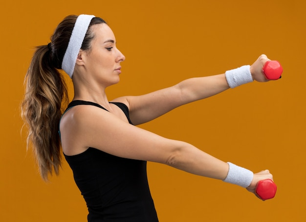 Jeune fille assez sportive confiante portant un bandeau et des bracelets