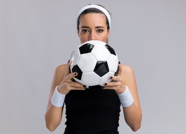 Jeune fille assez sportive portant un bandeau et des bracelets tenant un ballon de football par derrière