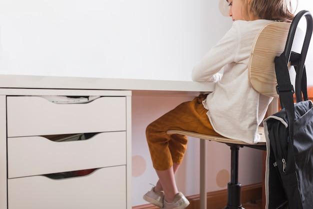 Jeune fille assise au bureau à la maison