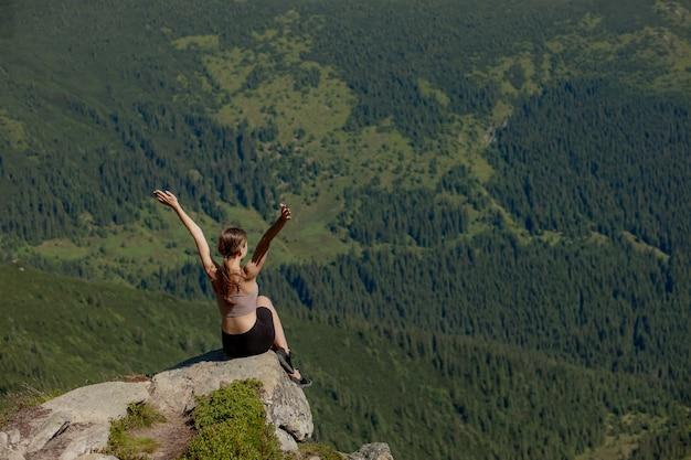La jeune fille assise au sommet de la montagne leva les mains sur la forêt. la femme a grimpé au sommet et a apprécié son succès.