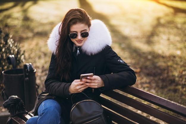 Jeune fille assise sur un banc et parler au téléphone