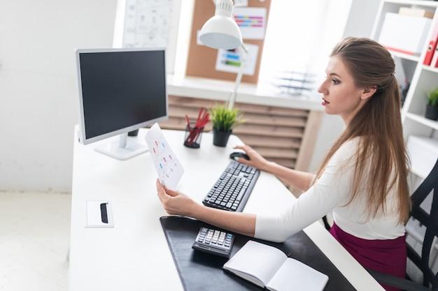 Une jeune fille assise à un bureau d'ordinateur et travaillant avec des documents.