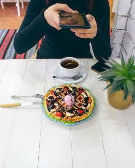 Jeune fille assise caffe en train de manger sa gaufre avec sa sauce au chocolat, ses tranches de banane et ses fraises sur une plaque en céramique verte et photographiée son petit-déjeuner