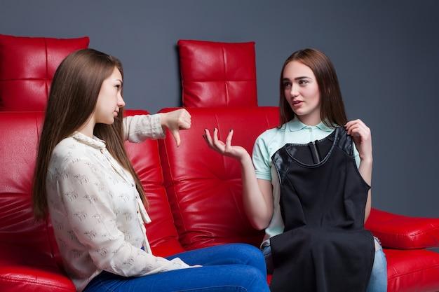 Jeune fille assise sur un canapé en cuir rouge et montre les costumes à la petite amie. loisirs de copines heureuses. amitié féminine