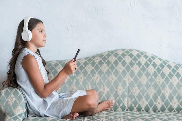 Jeune fille assise sur un canapé, écouter de la musique sur un casque