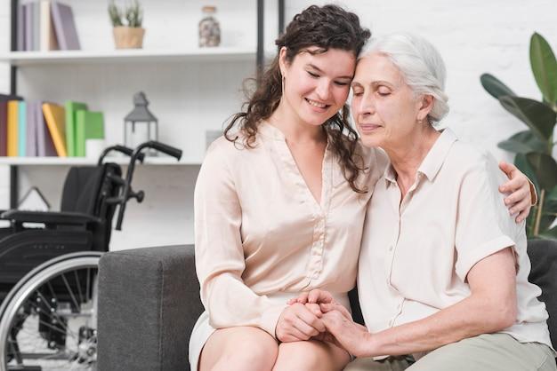 Jeune fille assise sur le canapé, embrassant sa mère