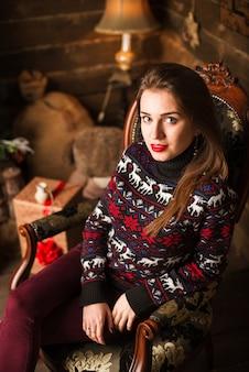 Jeune fille assise à côté d'un sapin de noël et de cadeaux