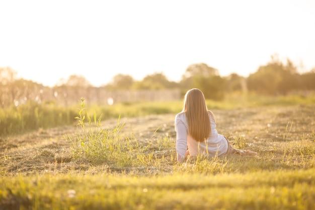 La jeune fille assise dans le champ. le concept de légèreté et sérénité, harmonie avec la nature
