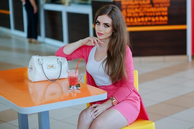 Jeune fille assise dans un restaurant avec un sac blanc et un soda