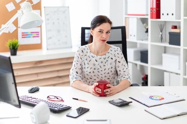 Une jeune fille assise devant un ordinateur bureau dans le bureau et tenant une tasse rouge.