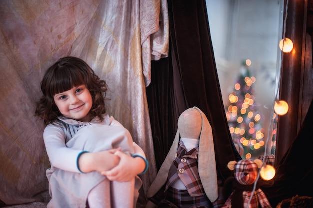 Jeune fille assise embrassant ses genoux à côté d'un miroir où guirlande de lumières
