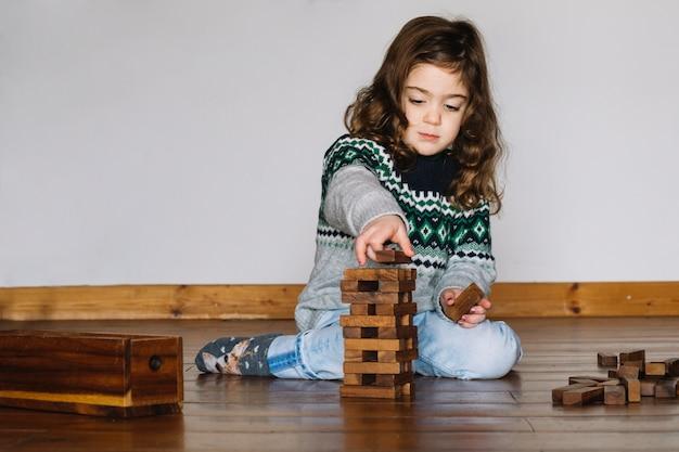 Jeune fille assise sur le plancher en bois empilant le bloc