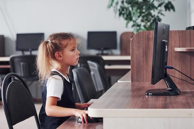 Jeune fille assise près du calcul et à la recherche d'informations