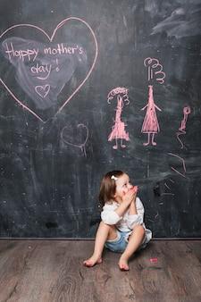 Jeune fille assise près de l'inscription de la fête des mères heureux