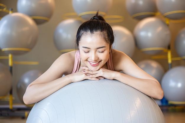 La jeune fille assise se détendre avec le ballon dans la salle de gym.